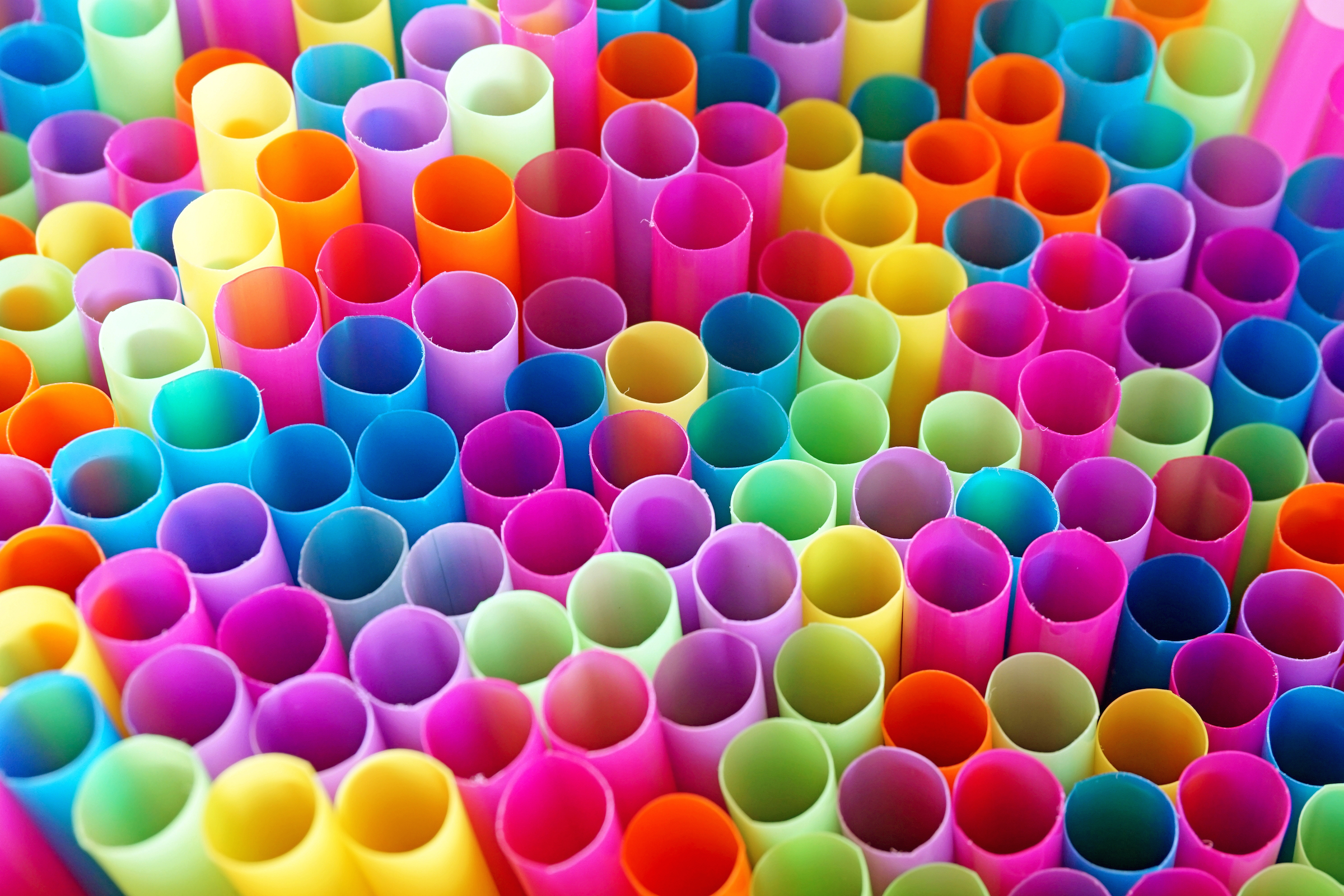 A bundle of colorful, paralell drinking straws.